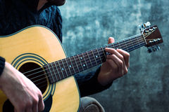 Young man playing an acoustic guitar on the background of a concrete wall.  Royalty Free Stock Image