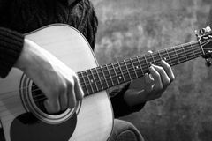 Young man playing an acoustic guitar on the background of a concrete wall.  Royalty Free Stock Photos