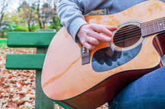 Young man playing acoustic guitar close up outdoors in autumn park Royalty Free Stock Photos