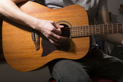 Young man playing on acoustic guitar Royalty Free Stock Image