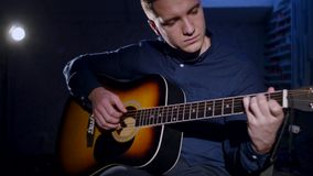 Young man playing acoustic guitar dark background Royalty Free Stock Photos