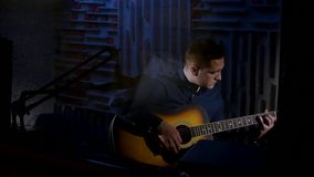 Young man playing acoustic guitar dark background in studio Stock Photography