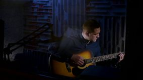 Young man playing acoustic guitar dark background in studio Stock Images