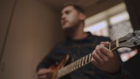 Young man playing an acoustic guitar at home with focus on hand and headstock. Musician playing acoustic guitar at home stock video footage