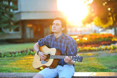 Young man playing on acoustic guitar in park Stock Photo