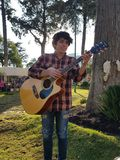 Young man playing the acoustic guitar in a park. Musician, musical instrument, music, pants with jeans and shirt Stock Images
