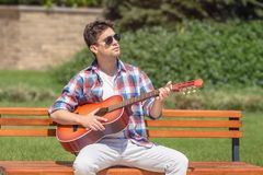 Young man playing acoustic guitar in the park. Urban fashionable guy sitting on bench in the park and playing acoustic guitar Royalty Free Stock Images