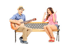 Young man playing acoustic guitar to his excited girlfriend seat. Young men playing acoustic guitar to his excited girlfriend seated on bench isolated on white Royalty Free Stock Photography