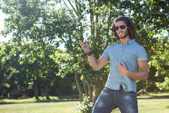 Young man playing air guitar in the park Stock Photography