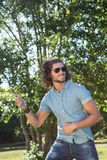 Young man playing air guitar in the park Royalty Free Stock Photo