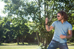 Young man playing air guitar in the park Royalty Free Stock Photos