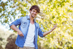 Young man playing air guitar in the park Royalty Free Stock Image