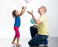 Young man playing with baby. Young men playing with baby in studio royalty free stock images