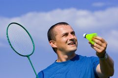Young man playing badminton. In a sunny day Stock Photos