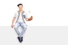 Young man playing with a baseball seated on panel Stock Photos