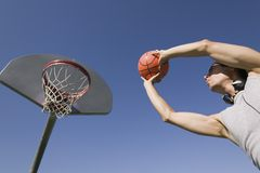 Young man playing basketball low angle view. Stock Photography
