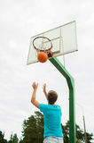Young man playing basketball outdoors. Sport, game and basketball concept - young man throwing ball into basket outdoors royalty free stock photo