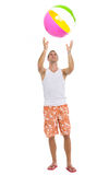 Young man playing with beach ball. Full length portrait of young man playing with beach ball Stock Images