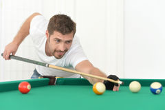 Young man playing billiard. Handsome young man playing billiard, balls on green table Stock Photo