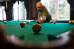 Young man playing billiard indoors. Spending free time on gambling. Young man playing russian billiard indoors. Spending free time on gambling Royalty Free Stock Photo