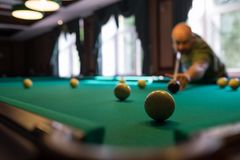 Young man playing billiard indoors. Spending free time on gambling. Young man playing russian billiard indoors. Spending free time on gambling Stock Photo