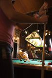 Young Man Playing Billiards. Young man lines up a pool shot with his competitor in the foreground. Vertical shot Royalty Free Stock Photos