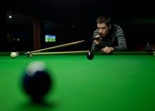 Young man playing billiards Stock Photos
