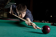 Young man playing billiards Stock Images