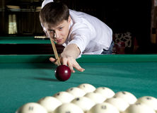 Young man playing billiards. In the dark billiard club Stock Photos