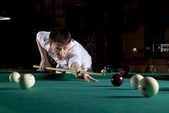 Young man playing billiards. In the dark billiard club Royalty Free Stock Photo
