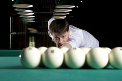 Young man playing billiards. In the dark billiard club Stock Image