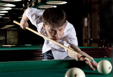 Young man playing billiards. In the dark billiard club Royalty Free Stock Photography