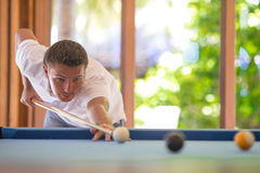 Young man playing billiards on summer vacation. Young happy man playing billiards on summer vacation Stock Photography