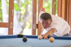 Young man playing billiards on summer vacation. Young happy man playing billiards on summer vacation Royalty Free Stock Photo
