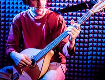 Young man playing on the bouzouki in sound recording studio.