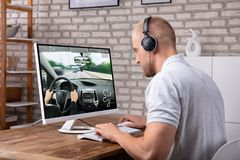 Young Man Playing Car Game On Computer. Young Man With Headphone Playing Car Game On Computer Over Desk royalty free stock photography