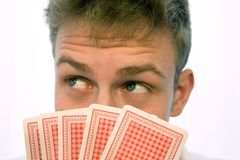 Young man playing cards. Probably poker, with a somewhat troughtful expression stock photo