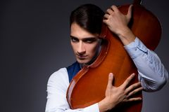 The young man playing cello in dark room Stock Images