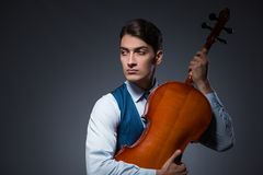 The young man playing cello in dark room Stock Image