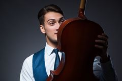 The young man playing cello in dark room Royalty Free Stock Photo