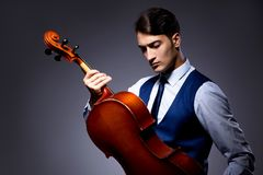 The young man playing cello in dark room Stock Photos
