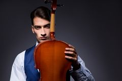 The young man playing cello in dark room Stock Photography