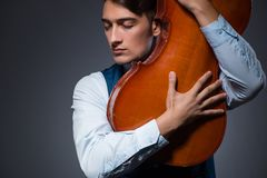The young man playing cello in dark room Royalty Free Stock Photos