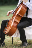 Young man playing cello outside. Cellist playing classical music on cello stock images