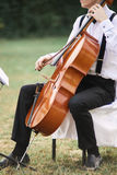 Young man playing cello outside. Cellist playing classical music on cello royalty free stock photo