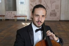 Young man playing the cello. Portrait of the cellist. Close-up royalty free stock images
