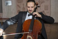 Young man playing the cello. Portrait of the cellist stock images