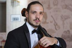 Young man playing the cello. Portrait of the cellist. Close-up royalty free stock image