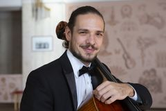 Young man playing the cello. Portrait of the cellist. Close-up stock photo