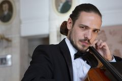 Young man playing the cello. Portrait of the cellist stock photos